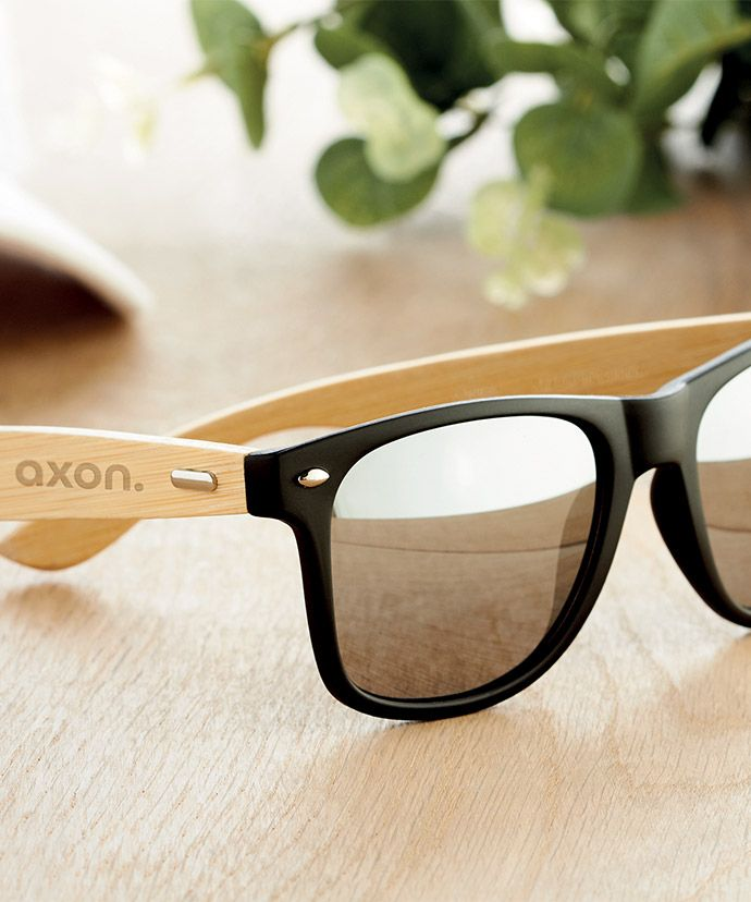 Solbriller med logo på et bord. Reklameartikler til sommeren.