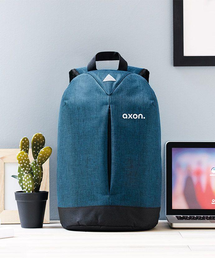 Blå rygsæk med logo på et bord med en bærbar og en plante. Reklameartikler til intern markedsføring.